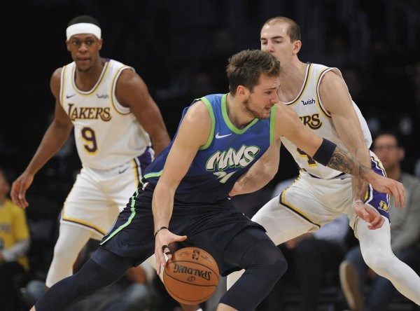 Luka Doncic (77) moves the ball against Los Angeles Lakers guard Alex Caruso (4) during the second half at Staples Center
